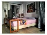 Tempat tidur dilengkapi dengan meja samping dan lampu baca